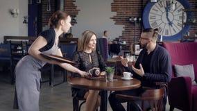 Kelner dostarcza rozkaz Żeński kelner dostarcza rozkaz dla potomstw dobiera się obsiadanie w kawiarni zdjęcie wideo