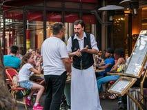Kelner i patron w intensywnej rozmowie przy chodniczek kawiarnią, Paryż Fotografia Royalty Free