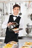 Kelner Lifting The Cover van Glazen kap Royalty-vrije Stock Afbeelding