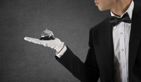 Kelner met in hand klok Concept de eerste klassendienst in uw zaken stock fotografie
