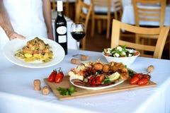 Kelner niesie talerze przy restauracją Zdjęcie Royalty Free