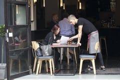 Kelner pomaga kobiety wybierać posiłek od menu Zdjęcie Royalty Free