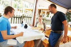 Kelner porci młodzi ludzie w restauraci Zdjęcia Royalty Free