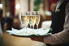 Kelner porci szampan na tacy przy Obrazy Stock