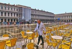 kelner przepustki przez żółtych krzeseł historyczny café po środku San Mark kwadrata zalewającego zdjęcie royalty free