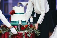 Kelner przynosi białego ślubnego tort na dekorującym stole Obrazy Stock