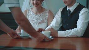 Kelner przynosi kawowych kubki nowożeńcy w górę które siedzą w kawiarni, zdjęcie wideo
