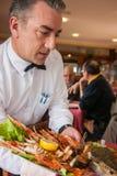 Kelner słuzyć naczynie z owoce morza Fotografia Stock