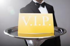 Kelner Showing Vip Text op Banner royalty-vrije stock afbeeldingen