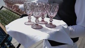 Kelner stawia dalej tace barwiących szklanych szkła dla alkoholicznych koktajli/lów i wino pomysły dla soku świeżego i wodnego 4k zbiory wideo