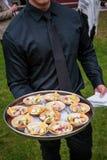 Kelner trzyma półmisek drewniani puchary z zakąskami pełno - poślubiać catering serie zdjęcie royalty free