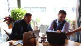 Kelner w restauraci przynosi rachunek stół dla dwa kolegi, biznesmeni Mężczyzna robi zapłacie przez NFC technologii dalej zbiory