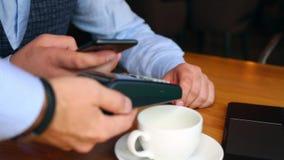 Kelner w restauraci przynosi rachunek stół dla mężczyzna Obsługuje robić zapłacie na telefonie komórkowym w kawiarni przez NFC te zbiory