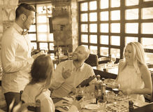 Kelner z restauracyjnymi gościami przy stołem Zdjęcie Royalty Free