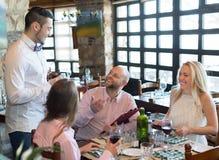 Kelner z restauracyjnymi gościami przy stołem Obrazy Royalty Free