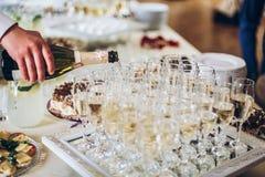 Kelnera dolewania szampan w eleganckich szkłach przy luksusowy ślubny ponownym Zdjęcie Royalty Free