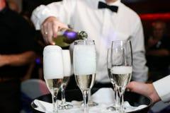 Kelnera dolewania szampan w szkłach przy ślubem Obrazy Royalty Free