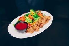 Kelnera kurczaka porcja Piec na grillu polędwicowy mięso z jarzynowym garnirunkiem t przy restauracją, zakończenie w górę widoku  zdjęcia stock