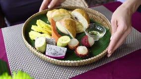 Kelnera serw ranku śniadanie z tropikalną owoc, croissant, blinem i miodem, obraz royalty free