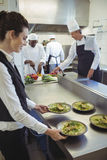 Kelnerka bierze jedzeń naczynia od rozkaz staci Obraz Stock