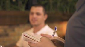 Kelnerka bierze rozkazu jedzenie od młodego człowieka i pisze notepad w wieczór restauracji zamkniętej w górę Rozkazuje jedzenie  zbiory