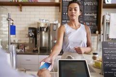 Kelnerka przy sklep z kawą bierze karcianą zapłatę od klienta obraz stock