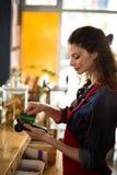 Kelnerka swiping kredytową kartę przez kredytowego czytnika kart przy kontuarem Obrazy Royalty Free
