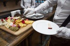 Kelners dienende kaas op een plaat Stock Foto's