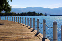 Kelowna Boardwalk. Back lit wide shot of boardwalk at edge of sparkling water of Okanagan Lake in Kelowna British Columbia Canada Waterfront Park on sunny summer Stock Photo