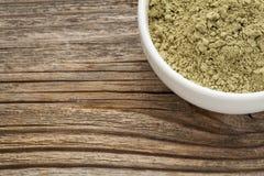 Kelp powder. Nutritional supplement reach in Iodine, Calcium, Iron, Potassium, Vitamin B1, B2, B12 and polysaccharides - ceramic bowl on grained wood stock image