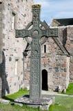 Keltisches Kreuz, das nahe alter Kirche steht Lizenzfreie Stockfotografie