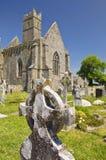 Keltisches Kreuz Irland, mit einer alten Abtei Stockfoto