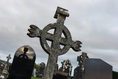 Keltisches Kreuz mit Reflexion auf Grabstein im Kirchhof, Irland, Nord-Europa Stockbild