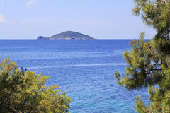 Kelyfos (Turtle) Island on horizon of the Aegean Sea. Stock Photo