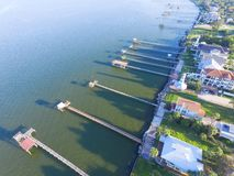 Kemah fishing piers aerial. Aerial view three-story waterfront vacation home with fishing piers stretching out over the Galveston Bay in Kemah city, Texas, USA Stock Photos