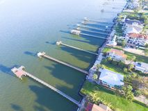 Kemah fishing piers aerial. Aerial view three-story waterfront vacation home with fishing piers stretching out over the Galveston Bay in Kemah city, Texas, USA Royalty Free Stock Photos