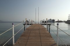 KEMER, TURKEY - MAY 07, 2018: pier overlooking the Mediterranean sea. KEMER, TURKEY-MAY 07, 2018: pier with wooden deck and metal handrails protruding into the stock images