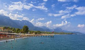 KEMER, TURKEY - OCT 1, 2017: People on the beach and mountains behind Stock Image