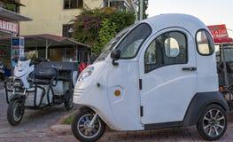 KEMER, TURQUIA - 2 DE OUTUBRO DE 2017: Mini carro para uma pessoa e uma motocicleta para o aluguel perto do armazenamento das mot imagens de stock