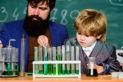 Kemi- och fysikbiologi fader och son på skola skäggig manlärare med pysen tillbaka skola till f?rklaring royaltyfri fotografi