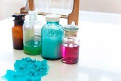 Kemiflaskor som innehåller olika vikter av olika färger som står på laboratoriumtabellen som ses över en hög av blåttpulver Arkivbilder