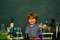 Kemikurs o Lycklig le elevteckning på skrivbordet biologiexperiment med mikroskopet arkivbilder