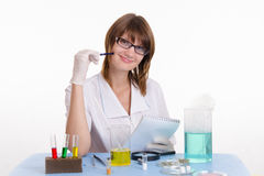 Kemiläraren tar anmärkningar i notepad Arkivfoton