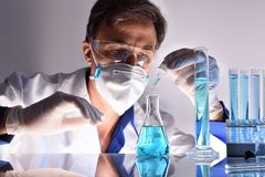 Kemisk arbetare som testar olika vikter bak ett laboratorium Royaltyfria Bilder
