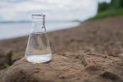 Kemisk flaska med vatten, sjön eller floden i bakgrunden Arkivfoton