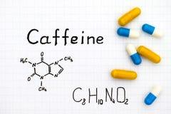 Kemisk formel av koffein med några preventivpillerar arkivfoto