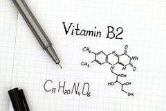 Kemisk formel av vitaminet B2 med pennan Arkivfoton