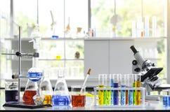 Kemisk vätskeprovrör och mikroskop i laboratorium arkivbilder