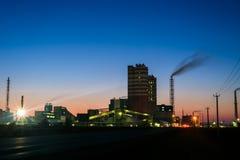 Kemisk växt i en konturbild på solnedgången, det glödande ljuset av den kemiska branschen på solnedgång- och skymninghimmel royaltyfria bilder