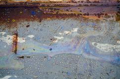 Kemiska fläckar för regnbåge på vattnet i en pöl på vägen royaltyfri bild